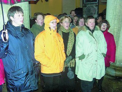 Gut gegen die Unbill des Wetters geschützt, stimmte der Schütte-Chor mit Advents- und Weihnachtsliedern auf das bevorstehende Fest ein. Foto: jp